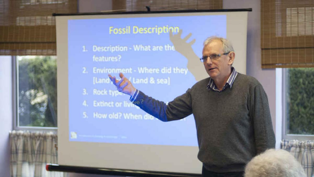 A man giving a presentation about fossils