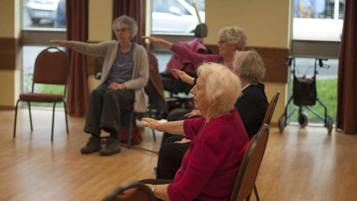 people being coached in chair based exercise