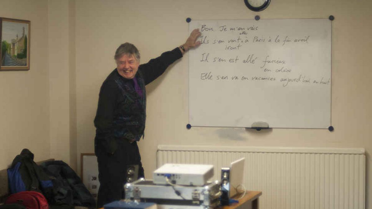 French language teacher pointing at white boad