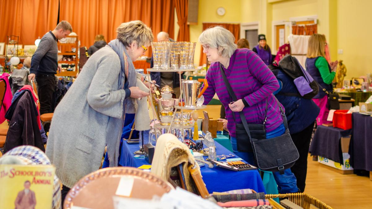 two ladies viewing items at the antiques fair