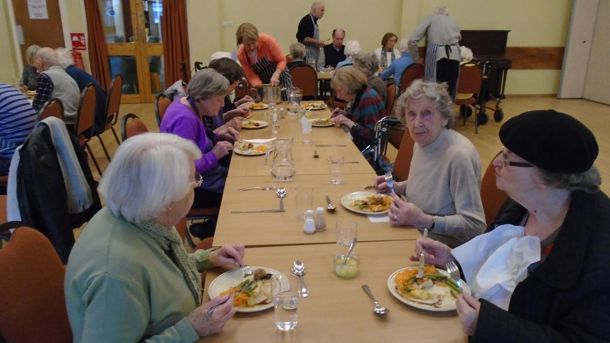 People sat eating on a long table CF Lunch Club