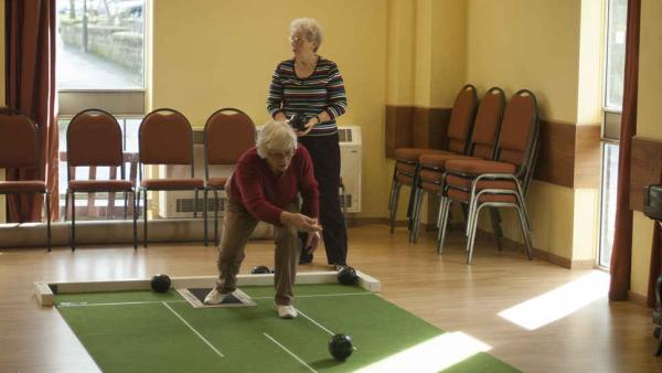 Two women play indoor bowls in the large hall